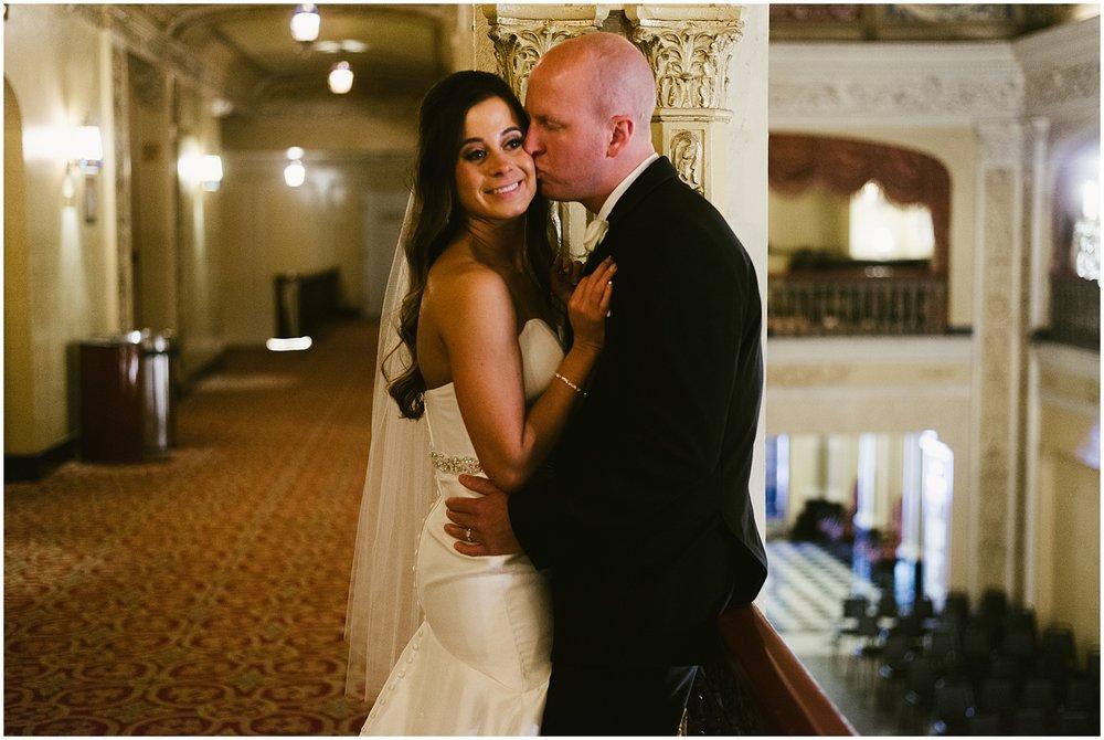 groom-kissing-brides-cheek-embassy-theatre-lobby-romantic-wedding