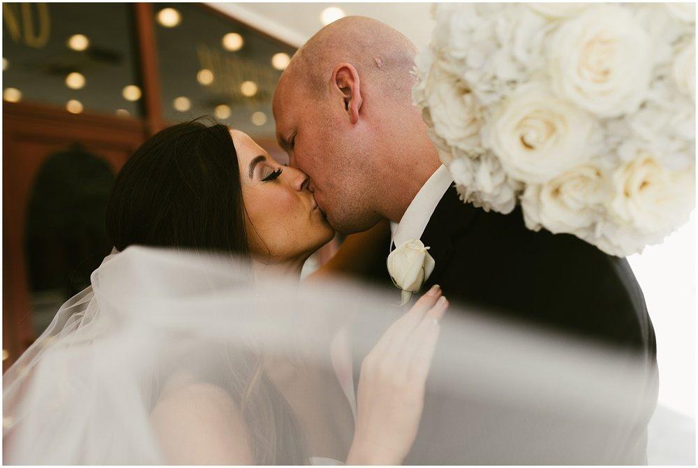 bride-groom-kissing-veil-embassy-theatre-lobby-romantic-wedding