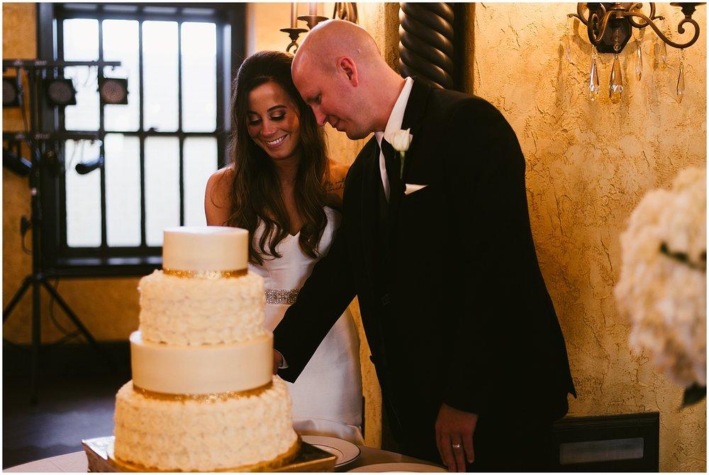 bride-smiling-cutting-cake-embassy-theatre-ballroom-fort-wayne-indiana-wedding-photographer