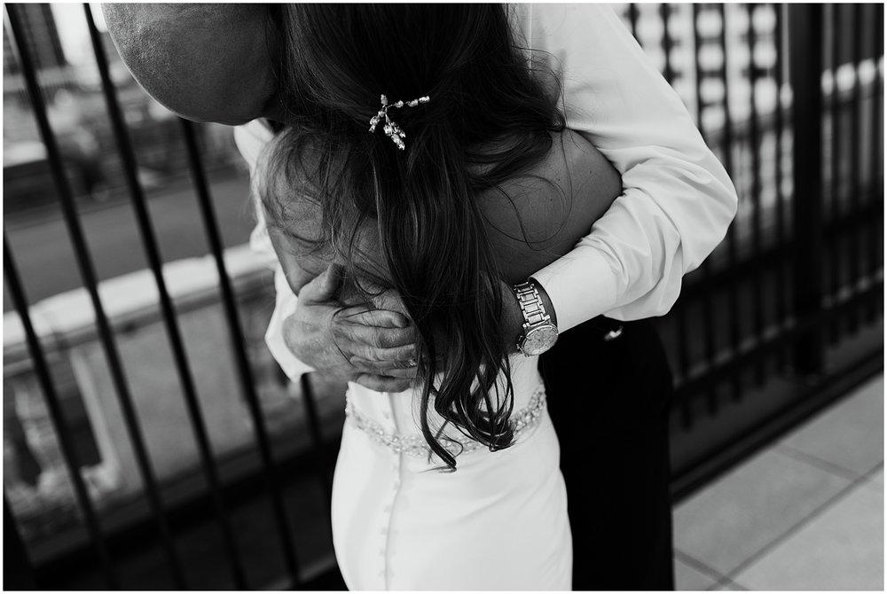 bride-groom-embracing-stella-york-gown-embassy-theatre-wedding-sunset-rooftop-bar-fort-wayne-indiana