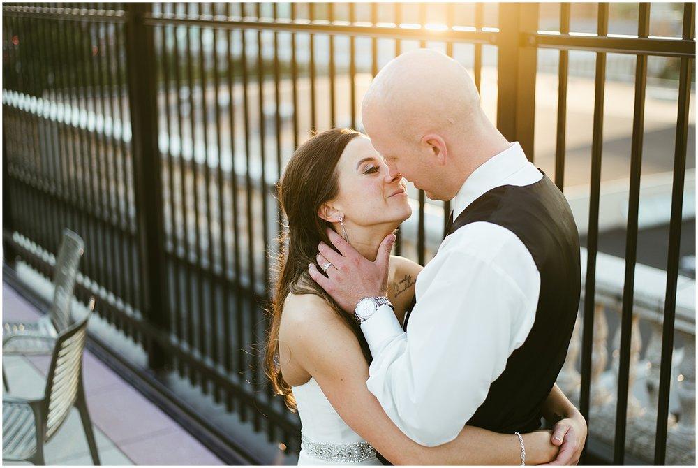 bride-groom-embrassing-sunset-embassy-theatre-wedding-sunset-rooftop-bar-fort-wayne-indiana