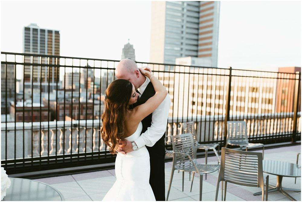 bride-groom-embracing-rooftop-embassy-theatre-fort-wayne-indiana-wedding-photographer