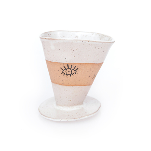 Ceramic, so its safe for your coffee. Sleep Eye Pour Over by Martina Thornhill.  You can grab this on Straw and Gold