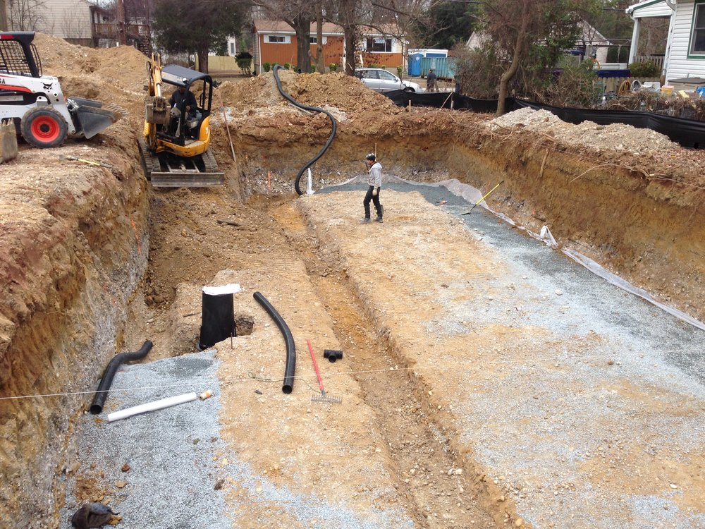 Perforated pipe snaking its way around the footing towards the sump pump basin. Also the footing for the interior load bearing wall has been excavated.