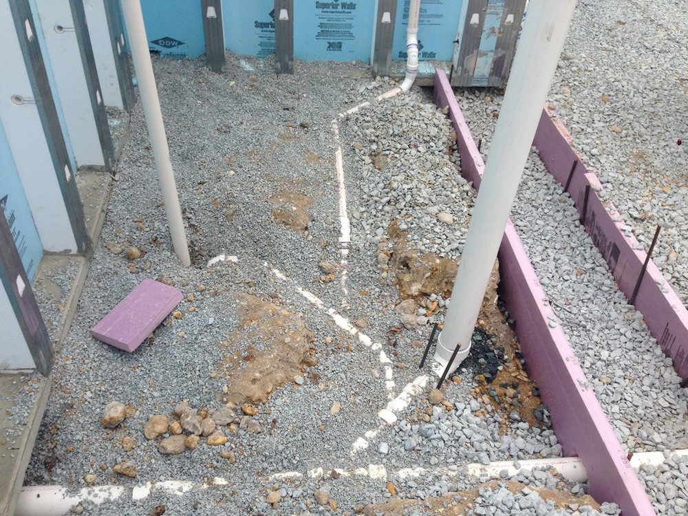 The rough plumbing is installed below grade with their p-traps and slopes.