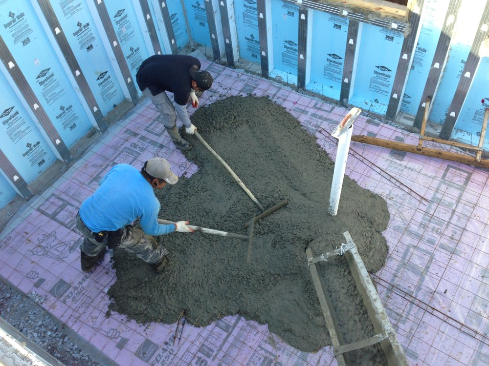"""Jose and the guys got a good back workout spreading the concrete around. The concrete goes on top of a plastic called a vapor barrier which in turn lies on top of 2"""" of Rigid Insulation providing the slab with even temperature which sits on top of 4""""-6"""" of compacted gravel which helps the underground water stay away from the slab."""
