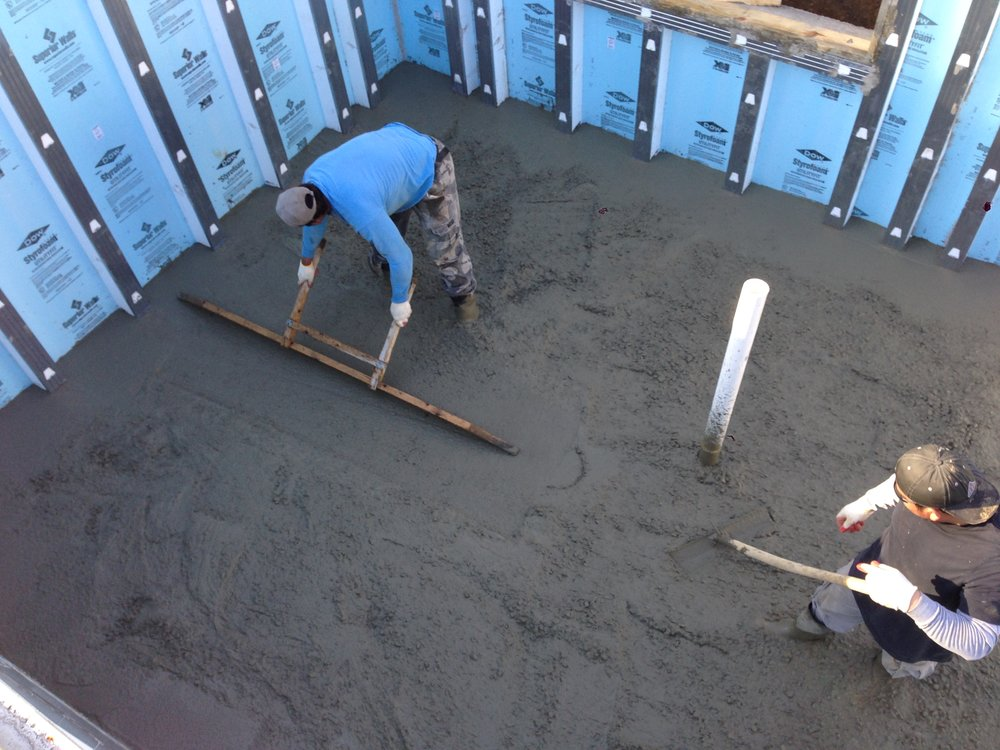 Jose leveling the slab. Each stud along the wall is marked with a chalk line and every 5' in each direction they place rebar at the correct slab height.