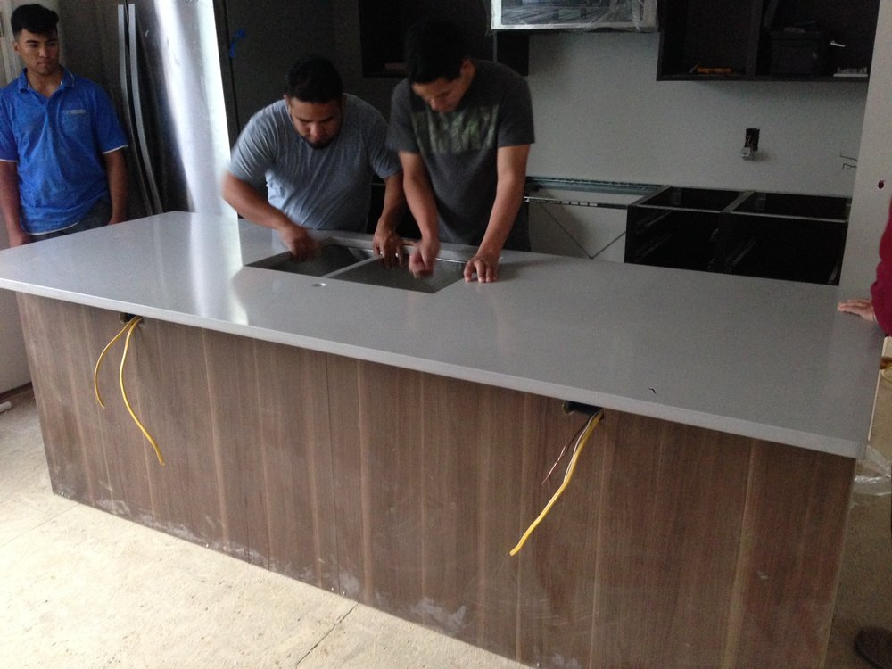 The undermount sink being installed with the counter top. Looking nice.