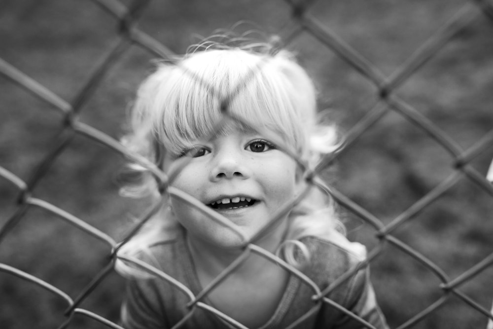 little girl through fence black and white portrait