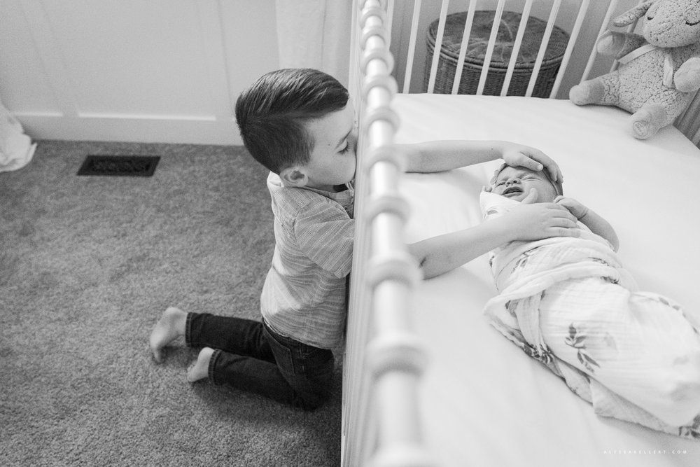 big brother reaching into crib to touch his baby newborn sister during photo session in mission bc