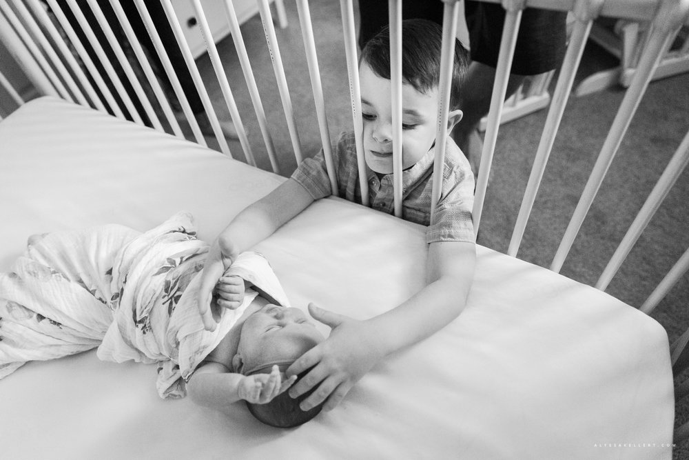 brother reaching in to crib through bars with his face squished during documentary photography session