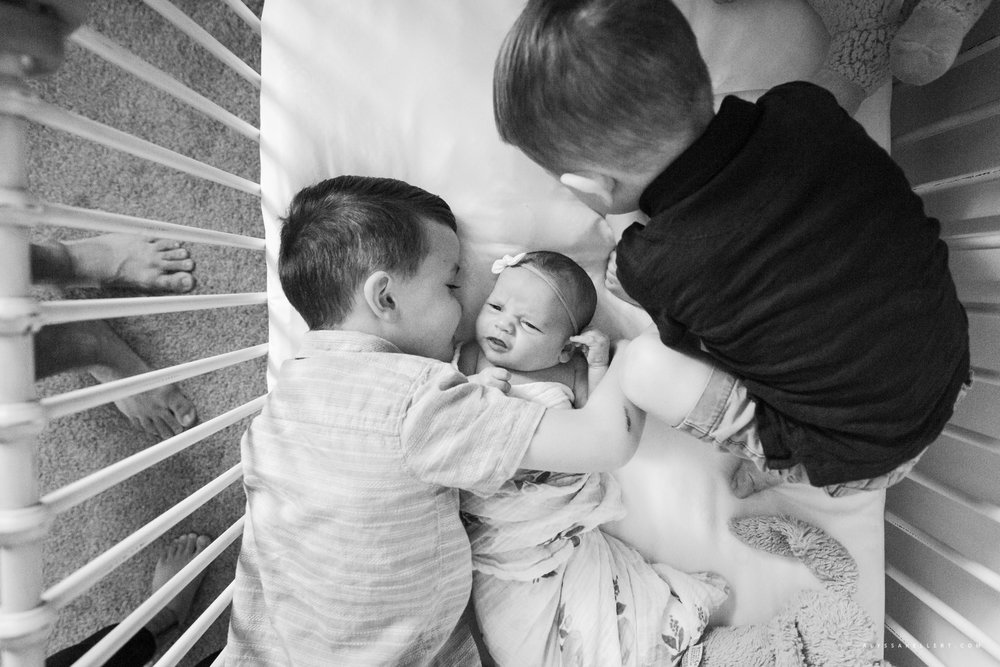 brothers cuddling baby sister in crib during documentary lifestyle session photography