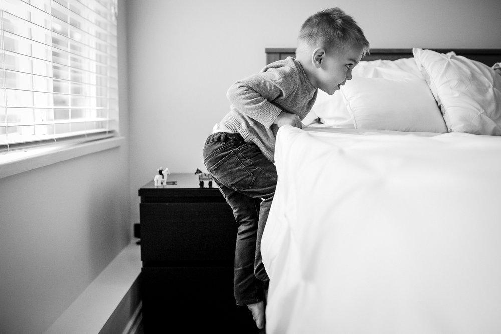 toddler-climbing-on-bed-family-photos.jpg