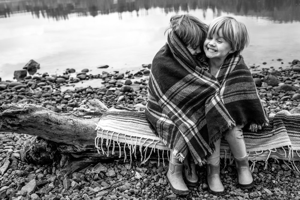 twin-girls-sitting-log-laughing-blanket-vancouver