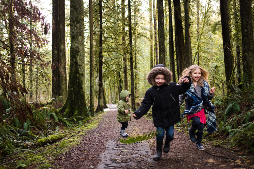 three kids running in forest with a fern in maple ridge