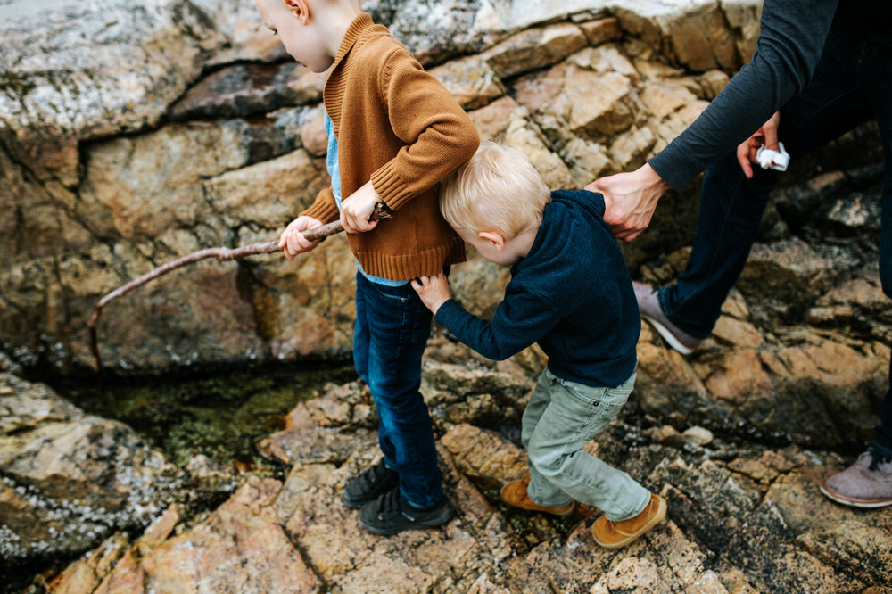 dad grabbing boy's arm as they walk along the rocks