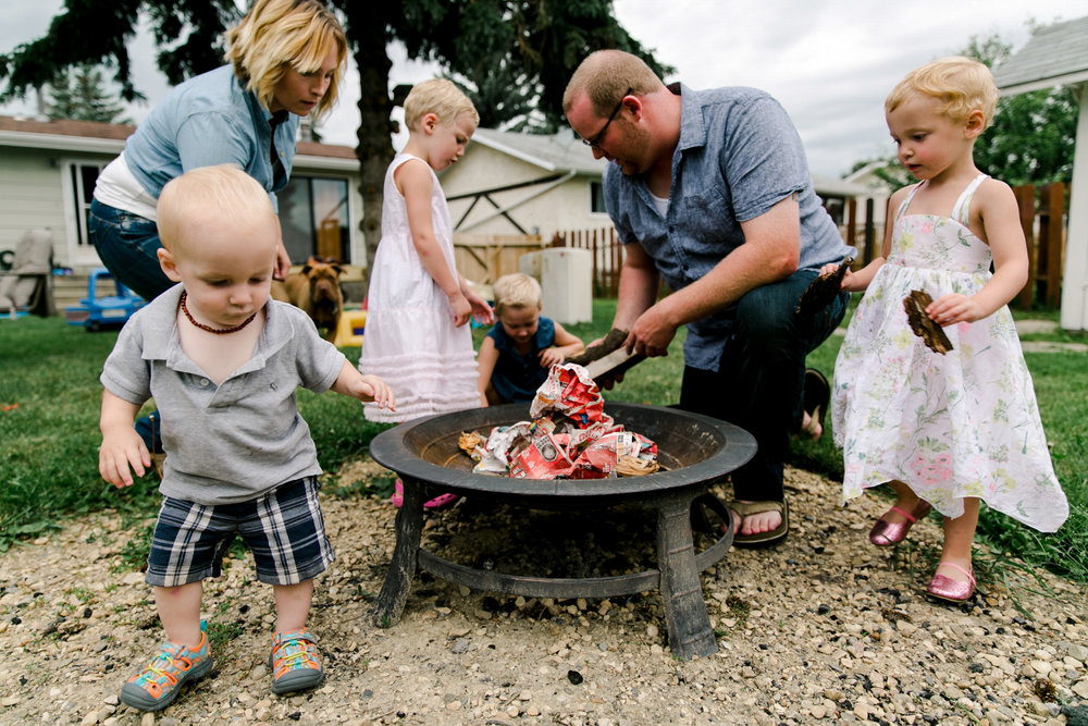 kids with parents at a camp fire in the back yard