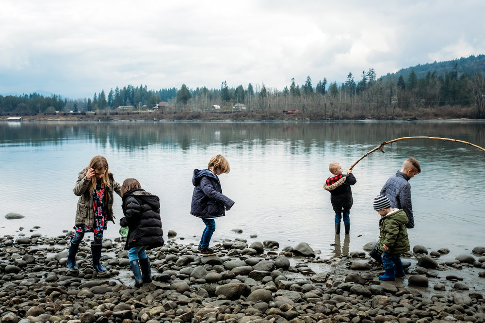 kids playing with sticks and rocks on the edge of a river in langley
