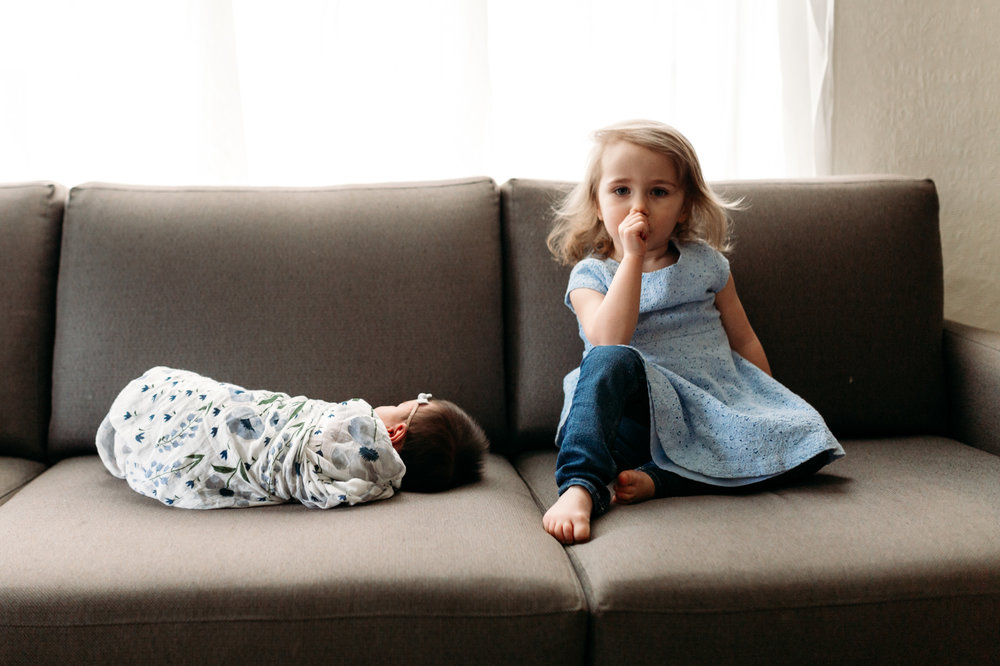 girl sitting beside baby sister on couch