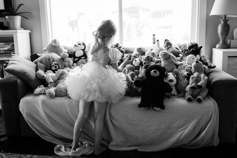 girl in tutu playing with stuffed animal audience