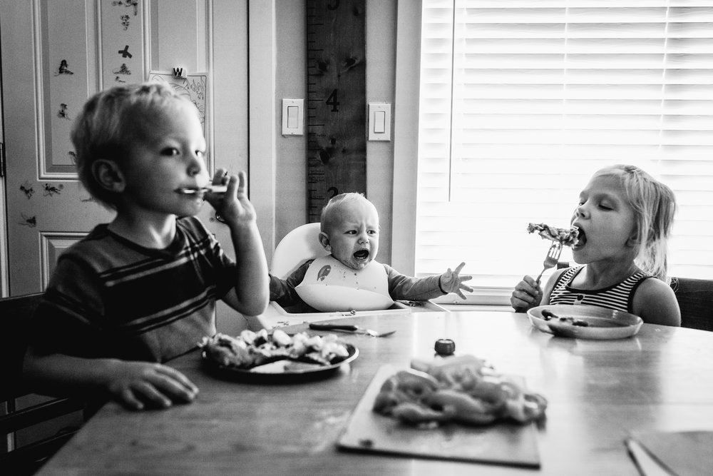 three kids eating with an angry baby