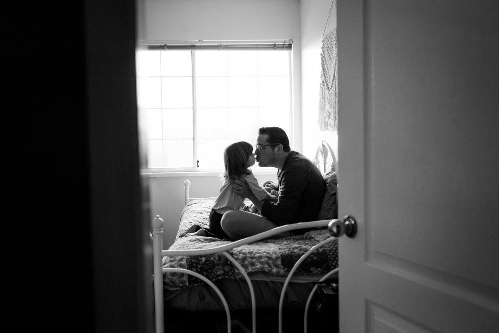 silhouette of dad holding newborn on bed, giving toddler a kiss
