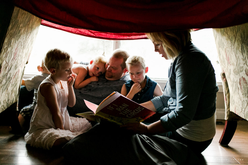 mom reading to kids under a tent in the living room