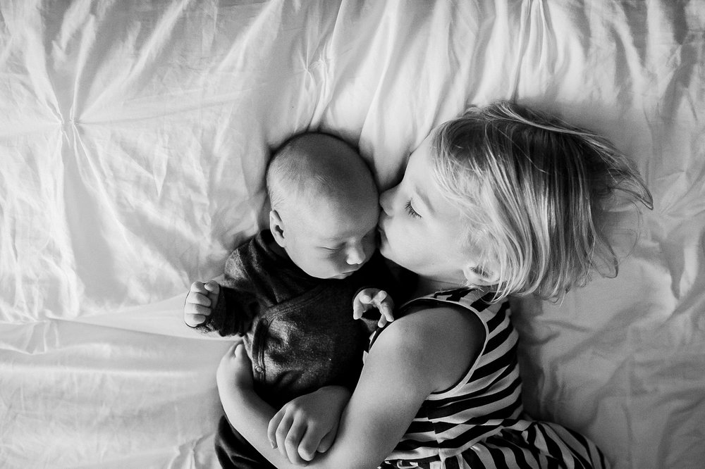 girl kissing baby brother on bed from above