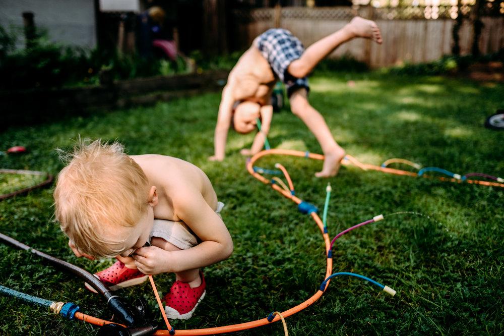 kids playing in sprinklers in the back yard maple ridge
