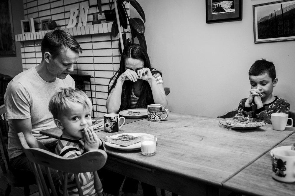 family sitting around table praying