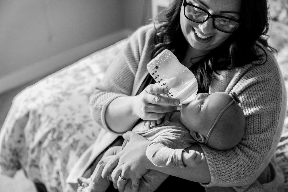 mom feeding baby with bottle on bed formula