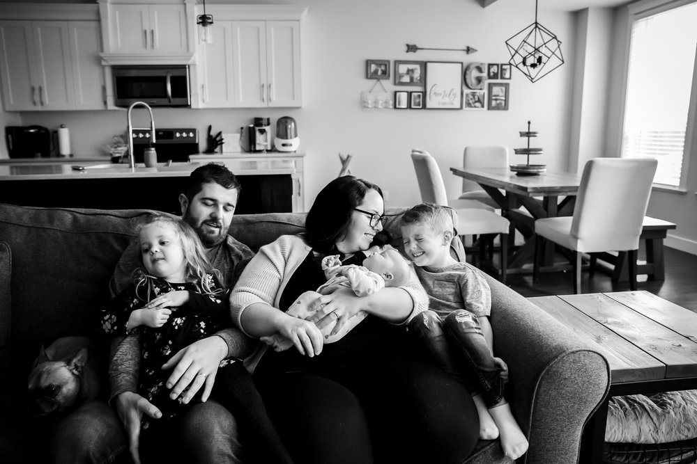 family and newborn sitting on couch snuggling together love newborn baby