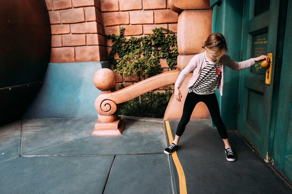 girl pulling on door knob at disneyland