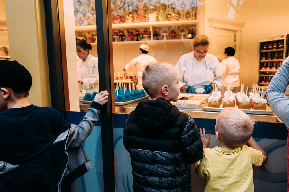 kids looking through window at workers making candied apples