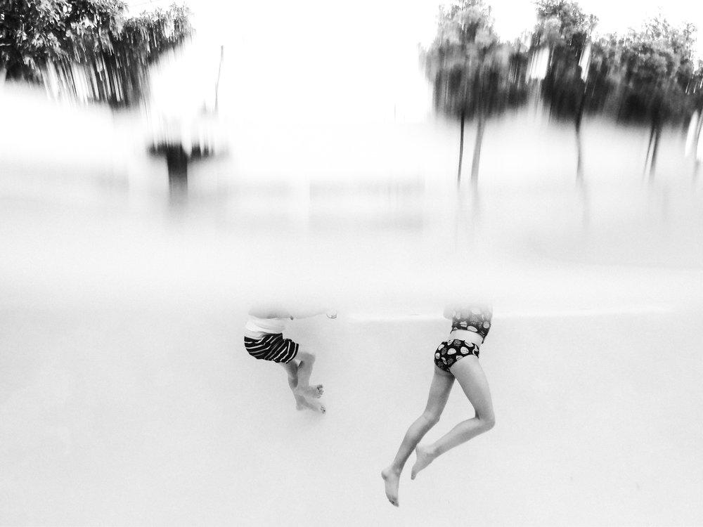 bottom half of kids swimming underwater