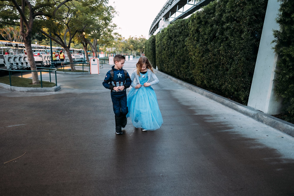 kids walking and talking wearing princess and captain america costume