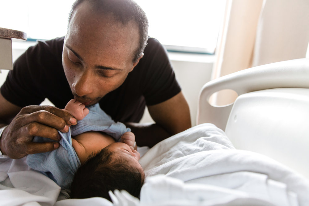 dad kissing newborn baby's hand on the hospital bed