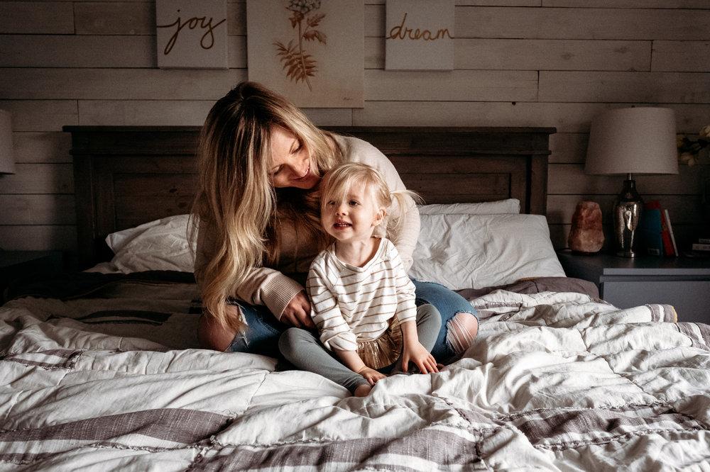 mom-snuggling-daughter-on-bed.jpg