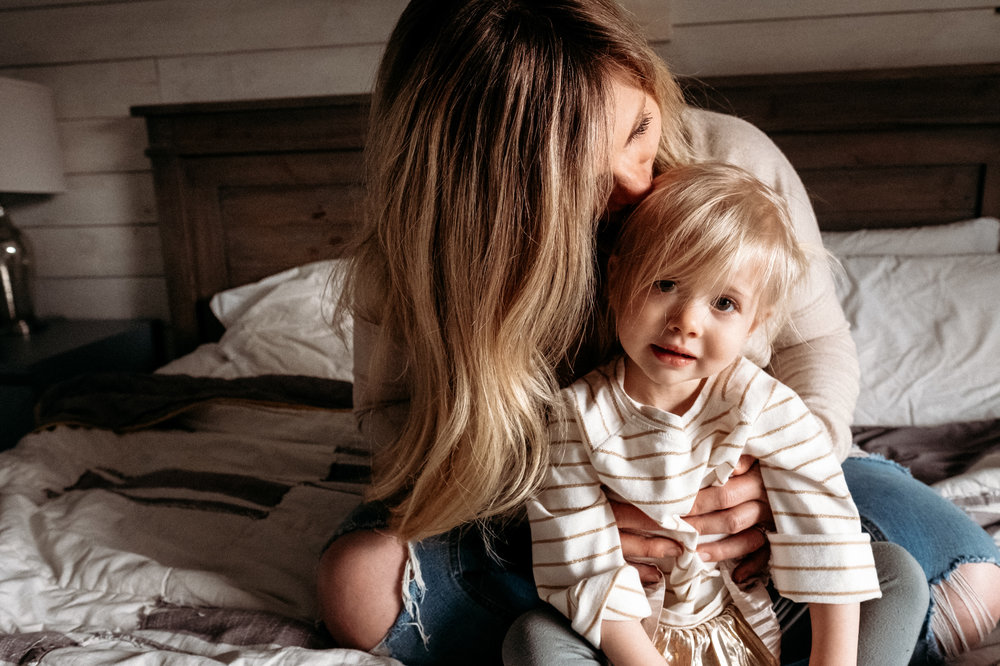 mom-kissing-daughter-head-on-bed.jpg