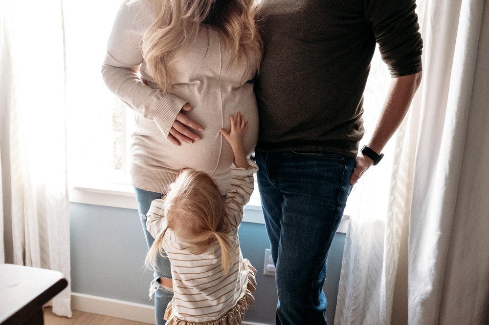 toddler-reaching-for-moms-pregnant-belly.jpg