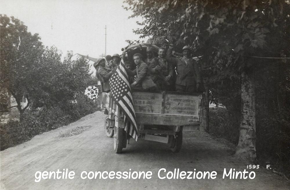 """Un camion di """"Arditi"""" dei Reparti d'Assalto italiani procede verso il Piave issando sul camion la Bandiera Statunitense"""