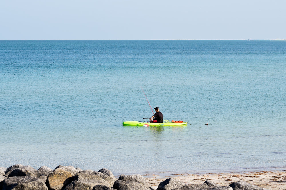 A young man fishing off his kayak and taking advantage of the great spring weather. The rock outcroppings are a great place to catch fish in this area. Fort Desoto offers kayak and canoe rentals by the hour or for the entire day.