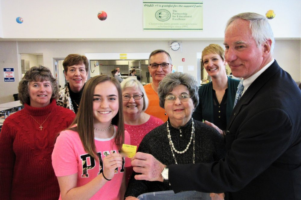 Megan Hatlee, GHS student who drew the winners' names, and John Fassero, president of the Partnership, hold the Seraphin family's winning ticket.  Looking on (left to right) are Partnership directors Susan Stromsland, Carole Scheller, Nanci Grandone, Don Throne, Rose Tebbe (treasurer), and Katie Ronald.