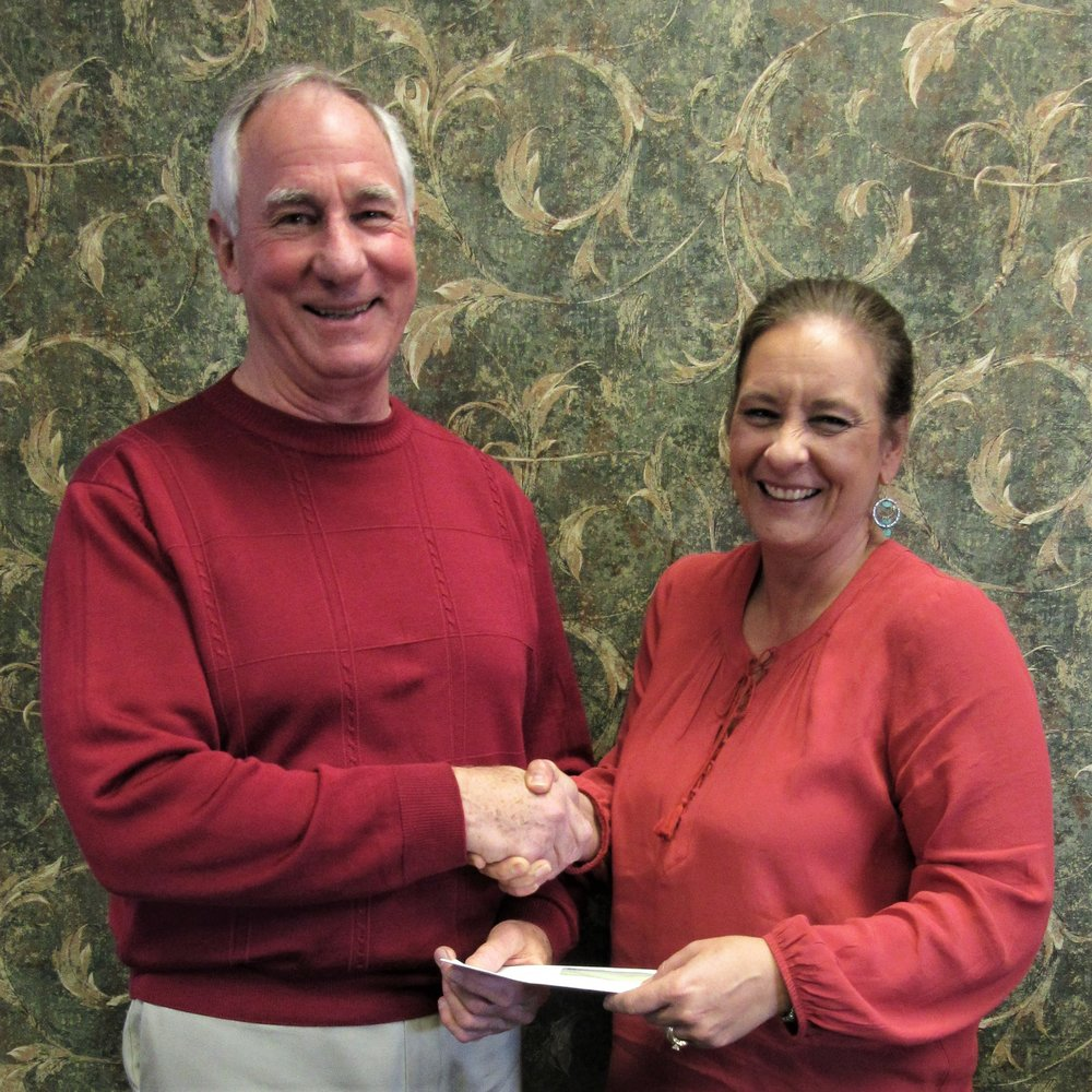 John Fassero, Jr., president of The Partnership, accepts a $2,000 donation from Jenni Alepra, Senior Vice President of United Community Bank's (UCB) Gillespie location.