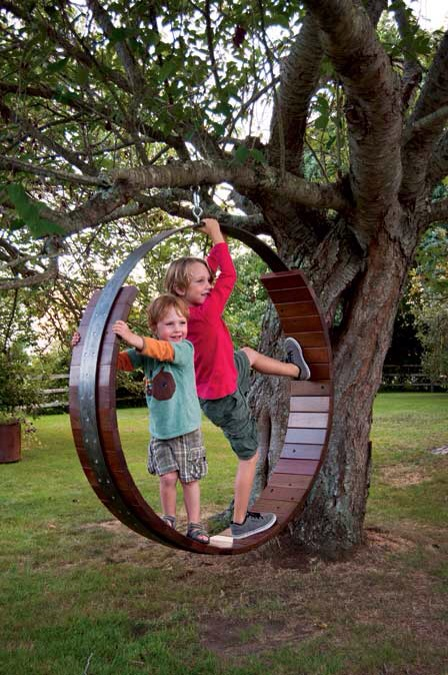 """""""The antique wagon wheel...is a favorite spot for catnaps. The iron rim holds a wooden seat made from a piece of the circa-1926 Coney Island boardwalk"""" -Yankee Magazine"""