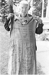 Dorothy Day holding up a prison dress. Photo courtesy of Jim Forest through a Creative Commons license.