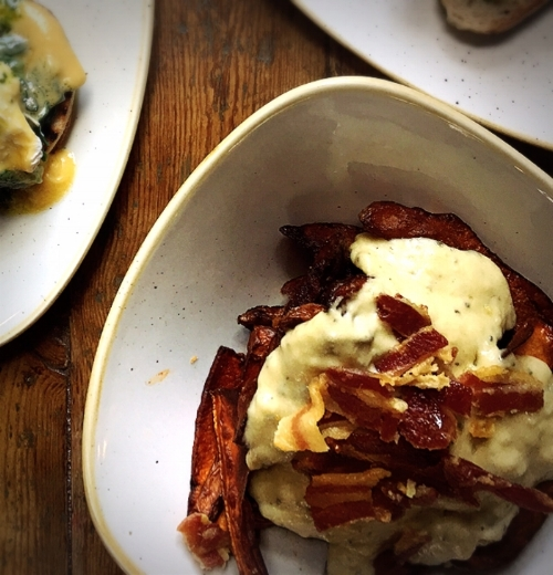 Image by  Kelly Chang ,KUMARA WEDGES topped with cheese sauce, bacon shards and sour cream
