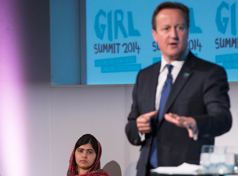 Malala Yousafzai watches on as UK Prime Minister David Cameron speaks.