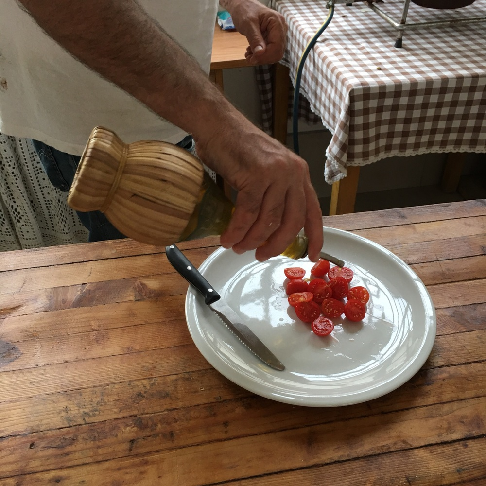 Luigi preparing samples of fresh cherry tomatoes with olive oil from their olive trees. They were sweet.