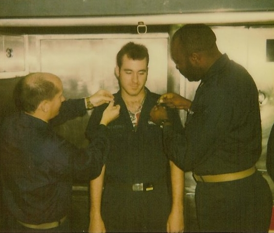 My captain and chief pinning on my Petty Officer 2nd Class rank emblems underway. Notice the tease of my Bob Marley shirt underneath.